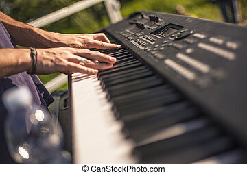 Hands of a musician play the keyboard
