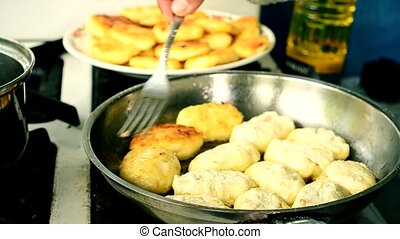 Hands of a person frying cottage cheese pancakes in a frying...
