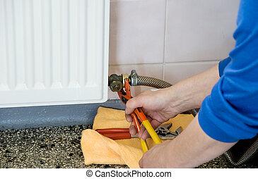 hands of a plumber repairman - hands of a plumber repairing...