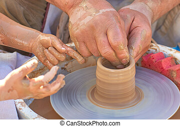 Hands of a potter and a student on clay, close-up