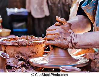 hands of a potter - potter working at a medieval fair,...
