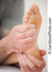 Hands of a practitioner holding a barefoot in a room