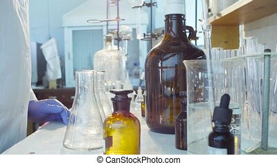 Hands of a scientist pouring solution into flasks - Chemical...