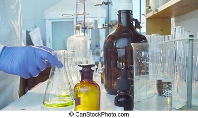 Hands of a scientist titrating solution - Chemical...