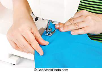 Hands of a seamstress at the sewing machine on a white background
