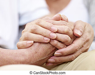 hands of a senior couple held together - close-up of hands...