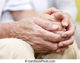 hands of a senior couple held together - close-up of...