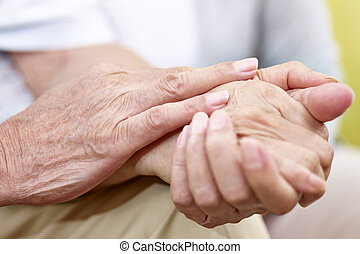 hands of a senior couple held together - close-up of a...