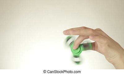 Hands of a teenage girl spin a green fidget spinner on white...