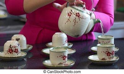 Hands of a Vietnamese woman prepares traditional Vietnamese tea at the bar