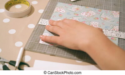 Hands of a woman crafting and scrap-booking christmas cards.