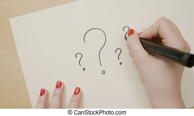 Hands of a woman drawing multiple question marks on a white paper using a black marker