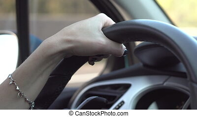 hands of a woman driver on the steering wheel of a car -...