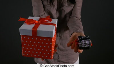 Hands of a woman holding a big gift box and a small gift box to choose from