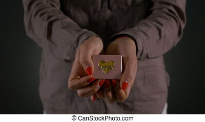 Hands of a woman holding and showing small gift box