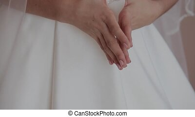 Hands of a woman in a white dress