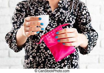 Hands of a woman putting menstrual cup into a bag