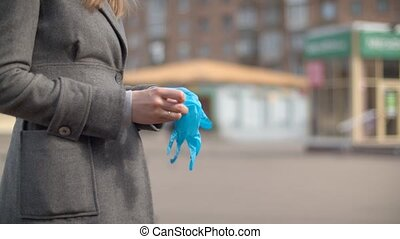 Hands of a woman putting on protective gloves
