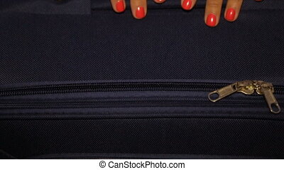 Hands of a woman with red manicure on luggage