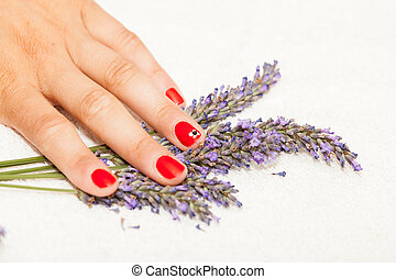 Hands of a woman with red nail polish posed by an esthetician