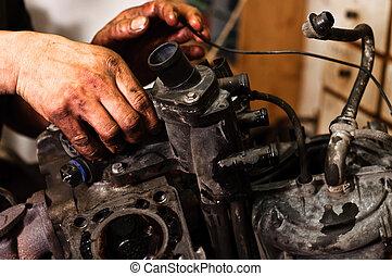Hands of a worker repairing broken engine