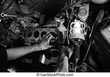 Hands of a worker repairing car