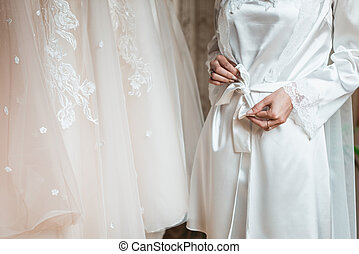 Hands of a young bride in a bathrobe. Bride preparation. Getting ready for wedding