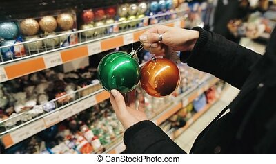 Hands of a young girl choosing multicolored balls for the Christmas tree in the market. A woman is bying colorful decorations in mall. Black friday concept.