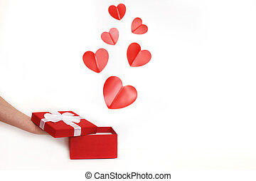 hands of a young man holding a present box with red hearts on a white background