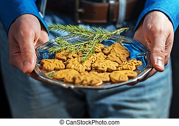 hands of a young man in jeans and an office shirt holds a silver dish with Christmas cookies piparkukas. The layout for the design of winter gifts.