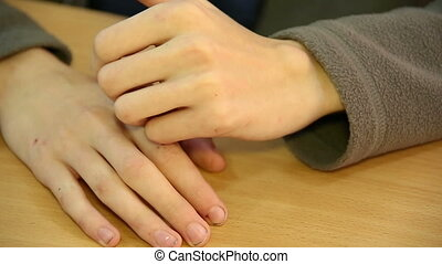 Hands of a young man on the Desk.