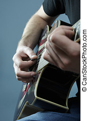 Hands of a young man playing a guitar with an American
