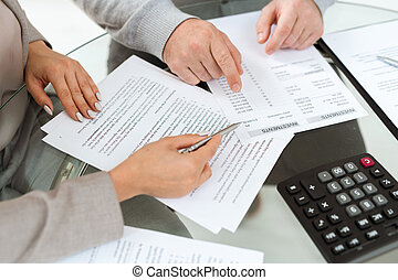 Hands of agent and mature man pointing at financial documents