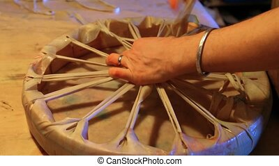 Close up footage of an artisan at work on a native drum. Stretching and tying the rawhide membrane over a wood frame.