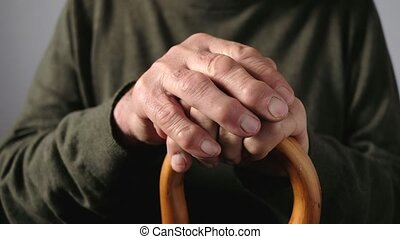 Hands of an elderly man on a walking cane or stick