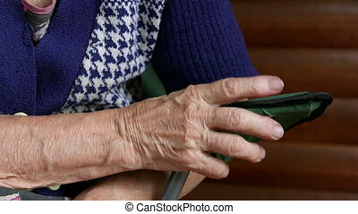 Hands of an elderly woman sitting in the chair