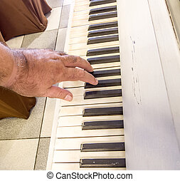 hands of an old musician play the piano