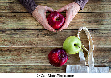 Hands of an old woman holding fresh organic apple. Eco Shopping Bag on wooden background, Flat Lay