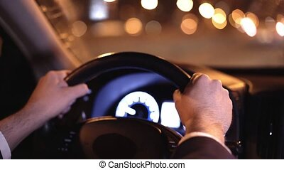 Hands of an unrecognizable businessman driving his car in a night city