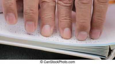 Hands Of Blind Man Reading Braille Language On Book -...