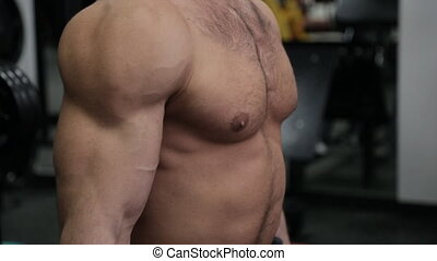 Hands of bodybuilder working with weights in the gym