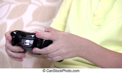 Hands of boy playing video games with a joystick, closeup -...
