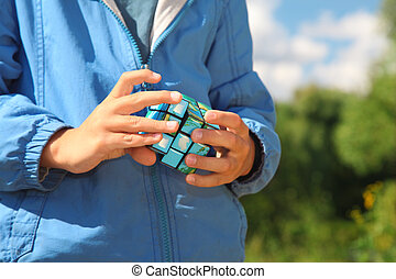 hands of boy  with magic cube outdoor in summer
