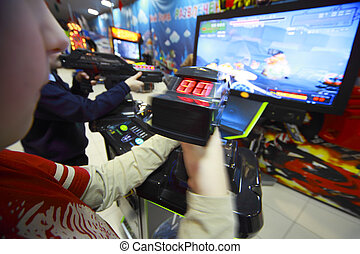 Hands of boys playing video games, they hold joystick in front of the monitor