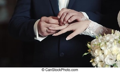 Hands of bride and groom exchanging wedding rings