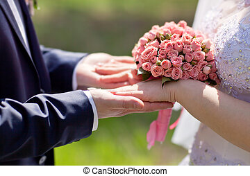Hands of bride and groom holding a bouquet of pink roses