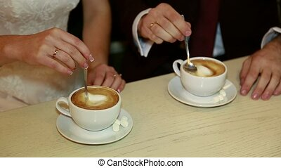 Hands of bride and groom holding a cup of coffee