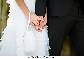 Hands of bride and groom in their wedding day