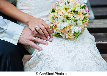hands of bride and groom with rings on wedding bouquet