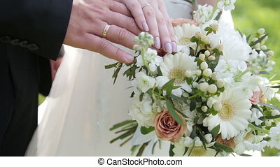 Hands of bride and groom with wedding rings and colourful bouquet